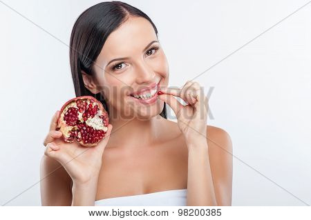 Pretty young girl is tasting fresh fruit