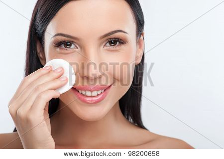 Attractive young girl is applying make-up on her face