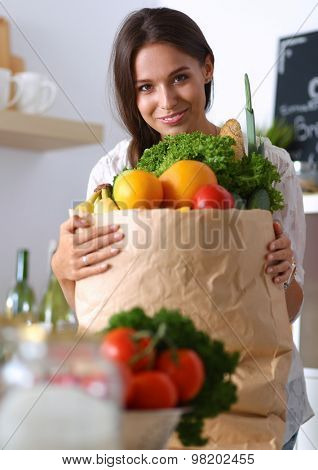 Young woman holding grocery shopping bag with vegetables and fruit .