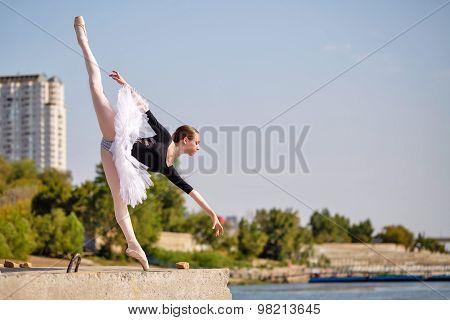 Slim Ballerina In Tutu Dancing On Promenade. Arabesque