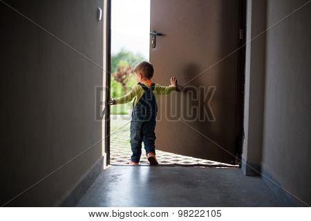 Little boy opens door
