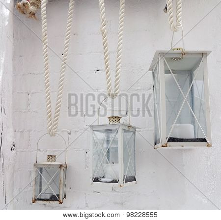 Three Candle Lamp On Rope Over White Brick Wall