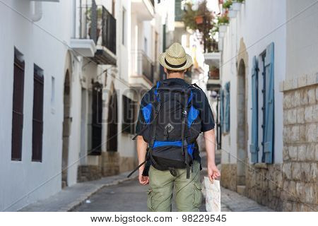Back Of Traveling Man Holding Map In Town