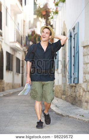 Smiling Male Traveler Walking In Town With Bag And Map