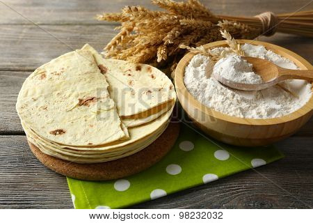 Stack of homemade whole wheat flour tortilla on cutting board, on wooden table background