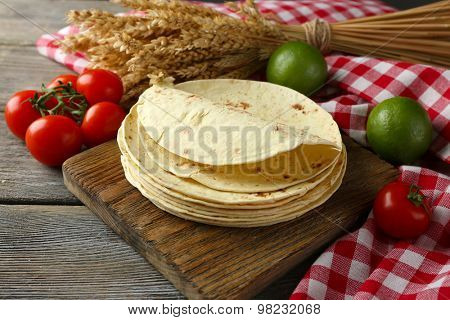Stack of homemade whole wheat flour tortilla and vegetables on cutting board, on wooden table background