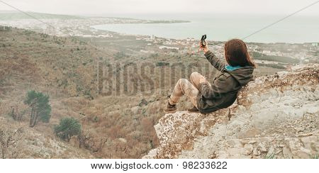Hiker Woman Sitting On Peak Of Mountain With A Compass