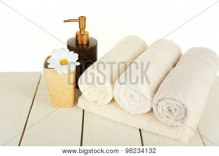 Soft towels with dispenser and flower on light background