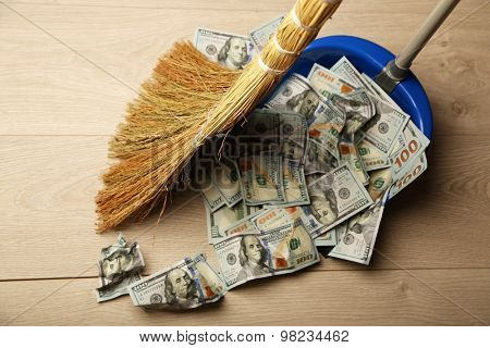 Broom sweeps dollars in garbage scoop on wooden floor background