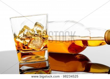 Glass Of Whiskey Near Bottle On Black Table With Reflection