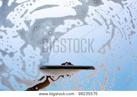 Washing window with soap and foam, closeup