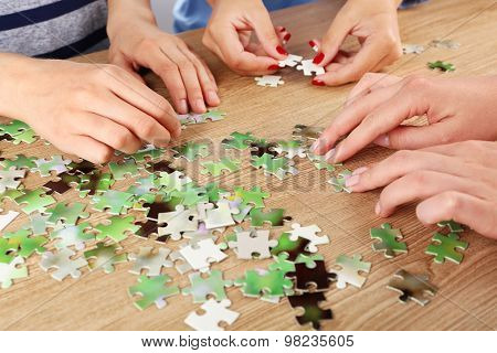 Female hands assembling puzzle on wooden table, closeup