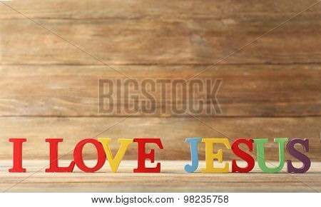 I LOVE JESUS sign illustrated with colorful plastic letters on wooden background