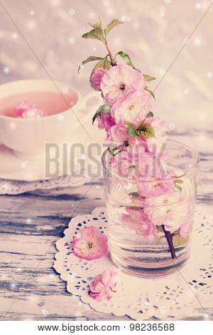 Beautiful fruit blossom in glass and tea cup on table on light background
