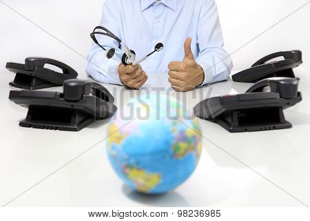 Global International Support Concept, Headset And Office Phone On Desk With Globe Map