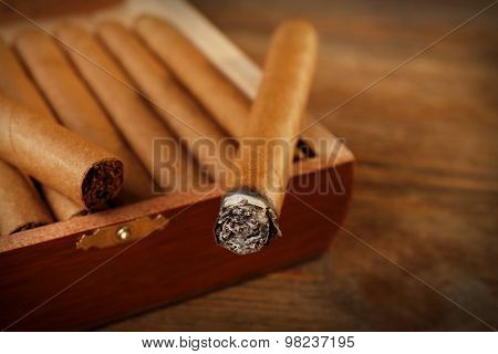 Cigars and burning one on wooden table, closeup