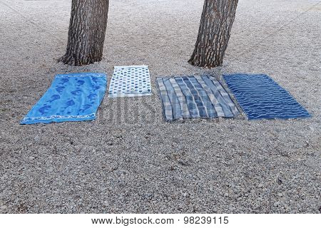 Four Blue Blankets With Differnt Textures On The Beach Below The Pine Trees