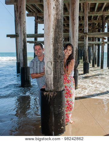 Playful couple under the pier