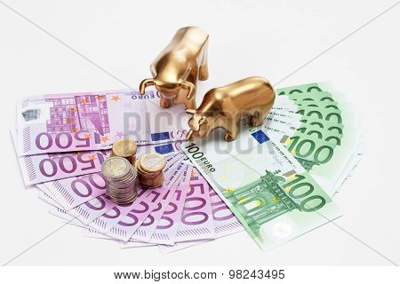 Golden Bear And Bull Figurines With Euro Coins On Fanned Euro Notes