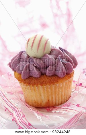 Close Up Of Buttercream Black Currant Cupcake With Chocolate Truffle