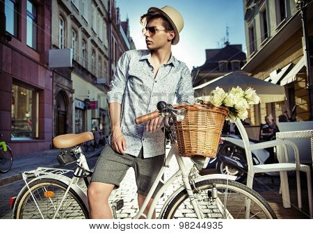 Handsome young man posing with a stylish bike