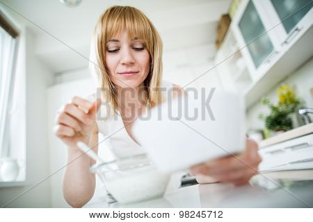 Young Blonde Woman Eating Muesli In Kitchen