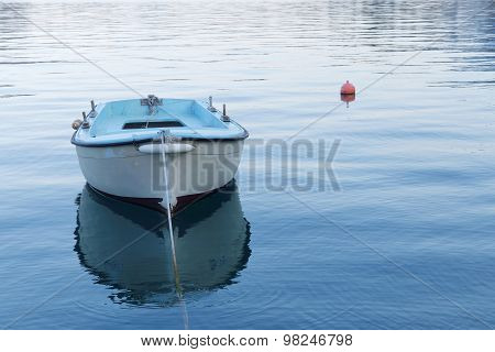Small Blue Fishing Boat In Calm Water