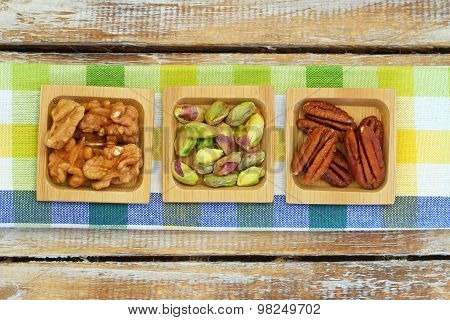 Pistachio, pecan nuts and walnuts on checkered cloth