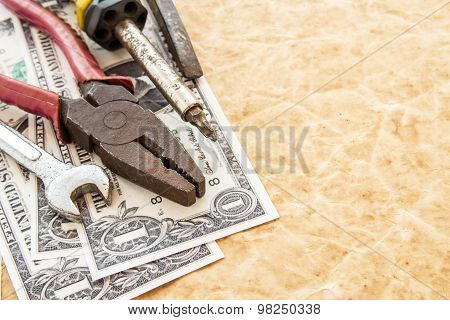 Dollar Banknotes And Tools On Old Paper Background