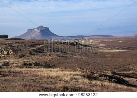 Dry Wintery Countryside With Mountainous Outcrop In Background