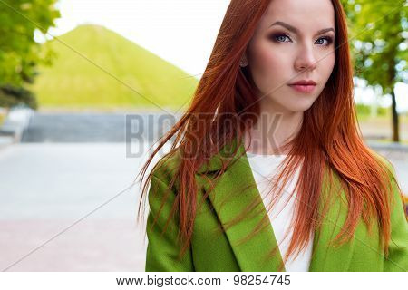 Beautiful sexy  red-haired girl in a green coat walking in the park