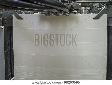 Stack of blank paper in a modern offset printing machine