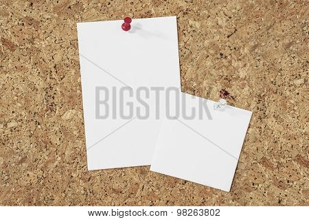 different paper notes pinned on a cork background