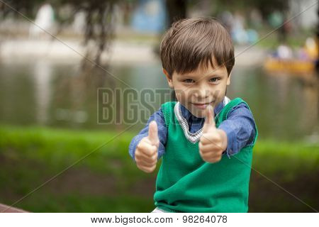 Little Boy with thumbs up on background summer park