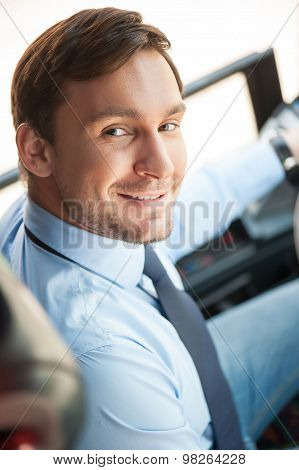 Cheerful young man is driving a public transport
