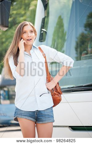 Cheerful young girl is using telephone near a bus
