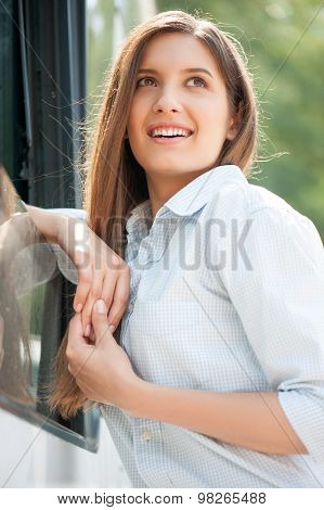 Cheerful young woman is using public transport