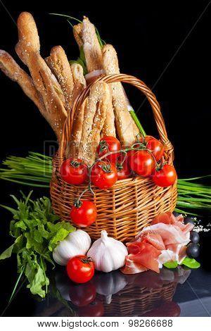 Grissini with prosciutto crudo in basket on black