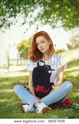 Cute redhead hipster girl sitting on grass with a black backpack