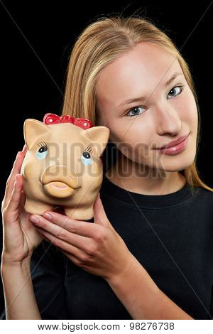 Young blonde woman holding a big piggy bank in her hands