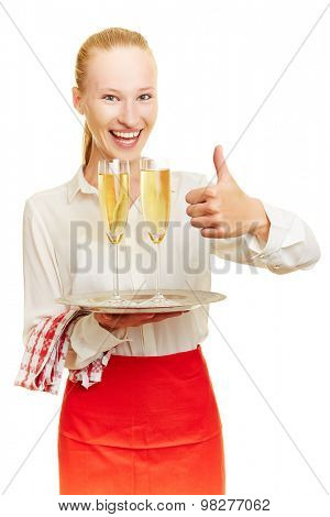 Happy female waiter with sparkling wine holding thumb up