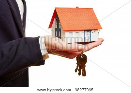 Real estate agent holding small house and keys in her hand