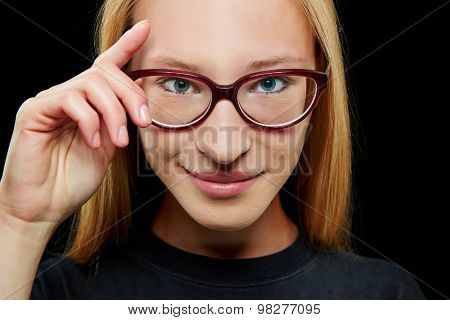 Smiling young blonde woman with her hand on her glasses