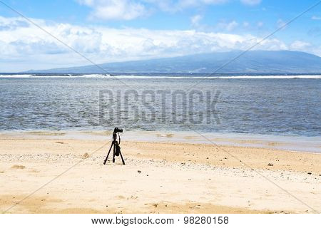 A camera and tripod on a deserted beach set to capture the ambiance of an empty natural wonder, with the island of Oahu outlining the horizon.
