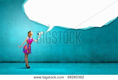 Young girl in multicolored bright dress with megaphone