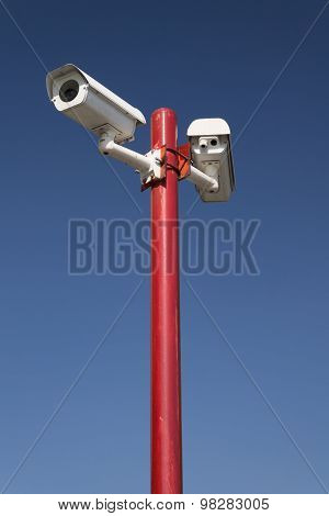 Security Camera On Red Pillar,blue Isolated.