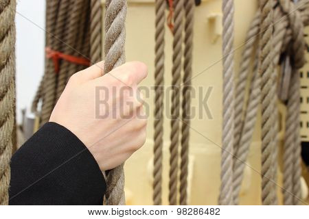 Hand Of Woman And Nautical Thick Rope On The Yacht