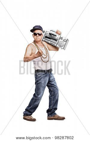 Full length portrait of a mature man in hip-hop outfit holding a ghetto blaster and looking at the camera isolated on white background