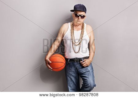 Grumpy senior in a hip-hop outfit holding a basketball, looking at the camera and leaning against a gray wall