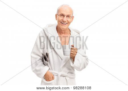 Senior man in a white bathrobe holding a newspaper and a coffee mug isolated on white background